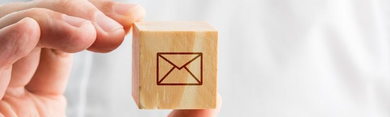 Un homme tient un cube avec le symbole d'une enveloppe